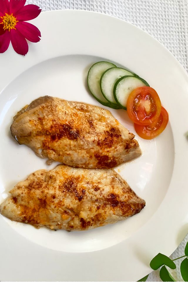 Air fryer tilapia in a plate with cucumber and tomatoes on the side